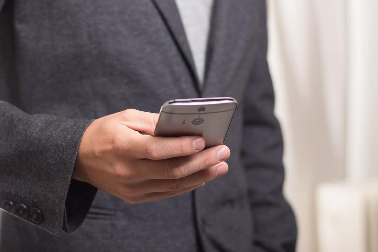 אדם אוחז טלפון סלולרי