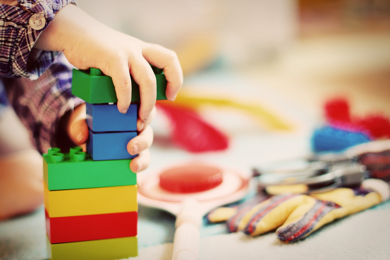 יד של ילד משחקת בצעצועים