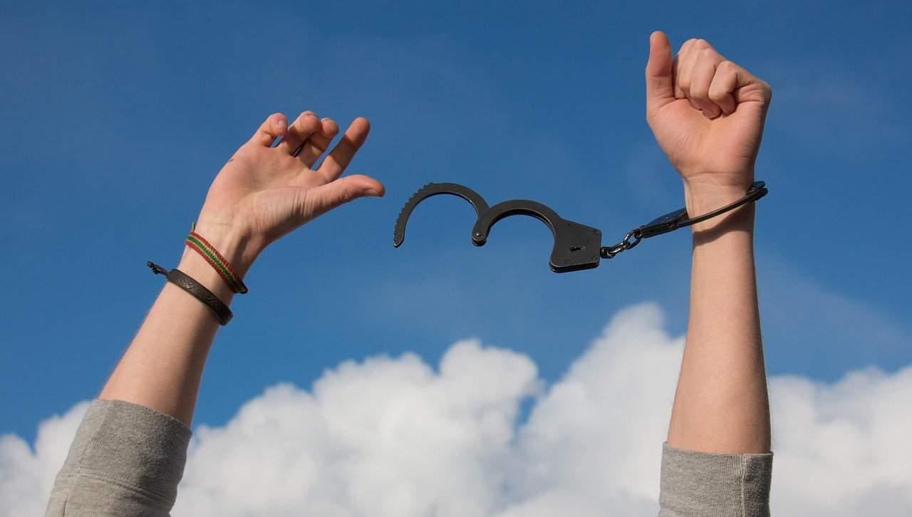 ידיים חופשיות מונפות באוויר כאשר אחת מהן כבולה לאזיקים