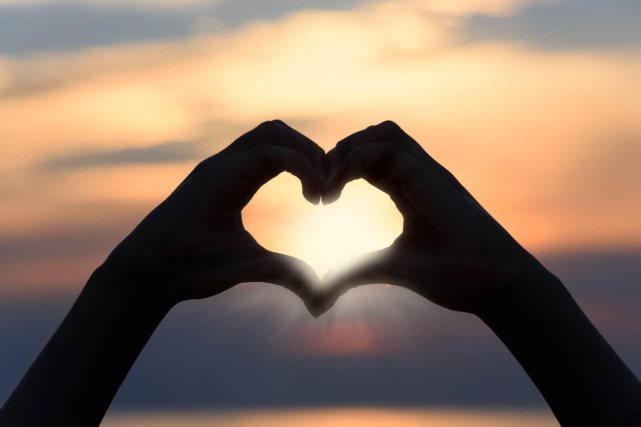 ידיים עושות צורת לב אל מול השקיעה