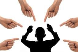 דמות עומדת ומופנות אליה אצבעות מאשימות