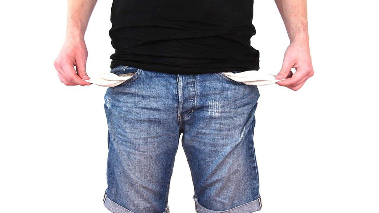 אדם מראה את תוכן כיסי מכנסיו הריק