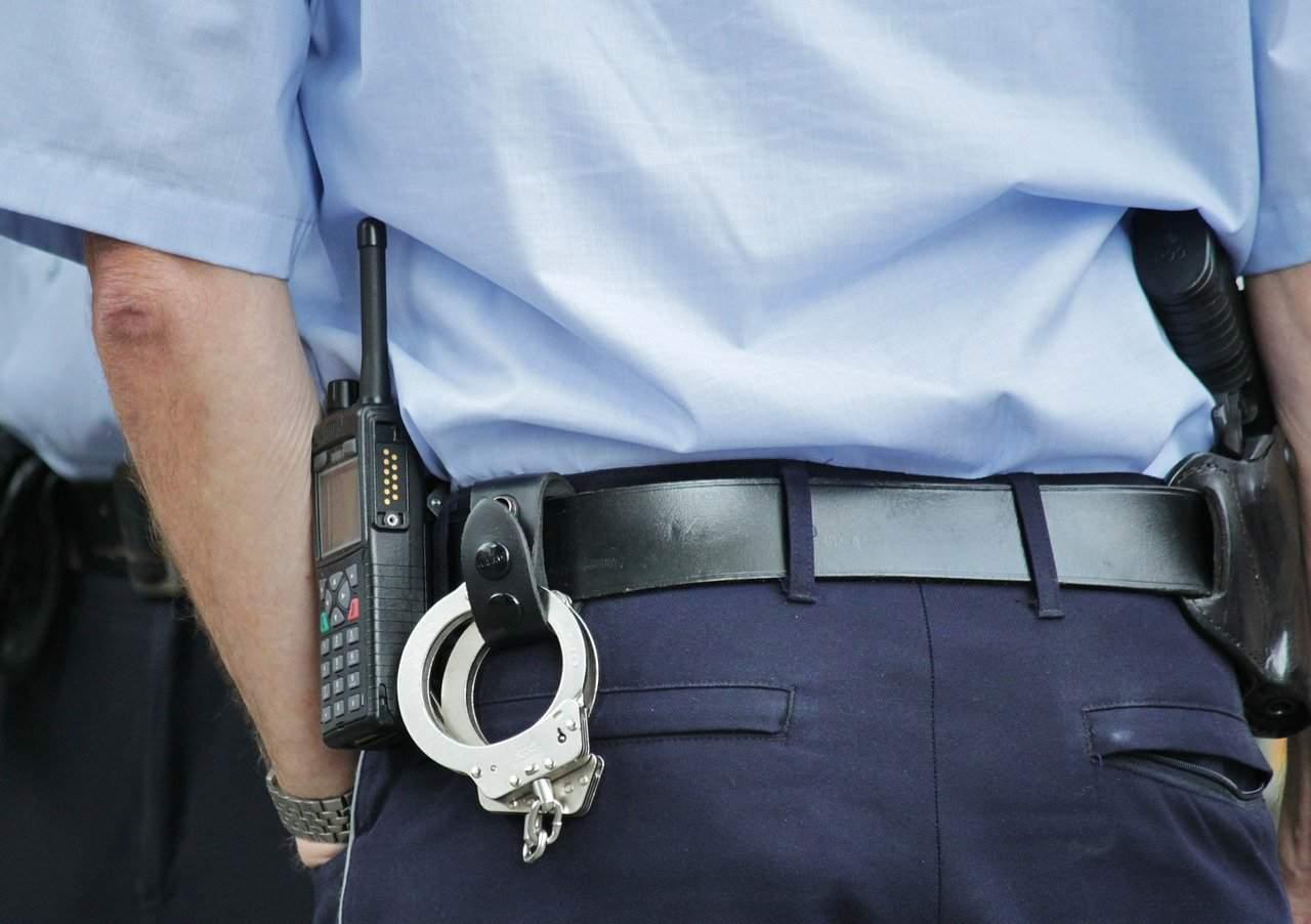אזיקים ומכשיר קשר תלויים על חגורת שוטר בתצלום על גבו