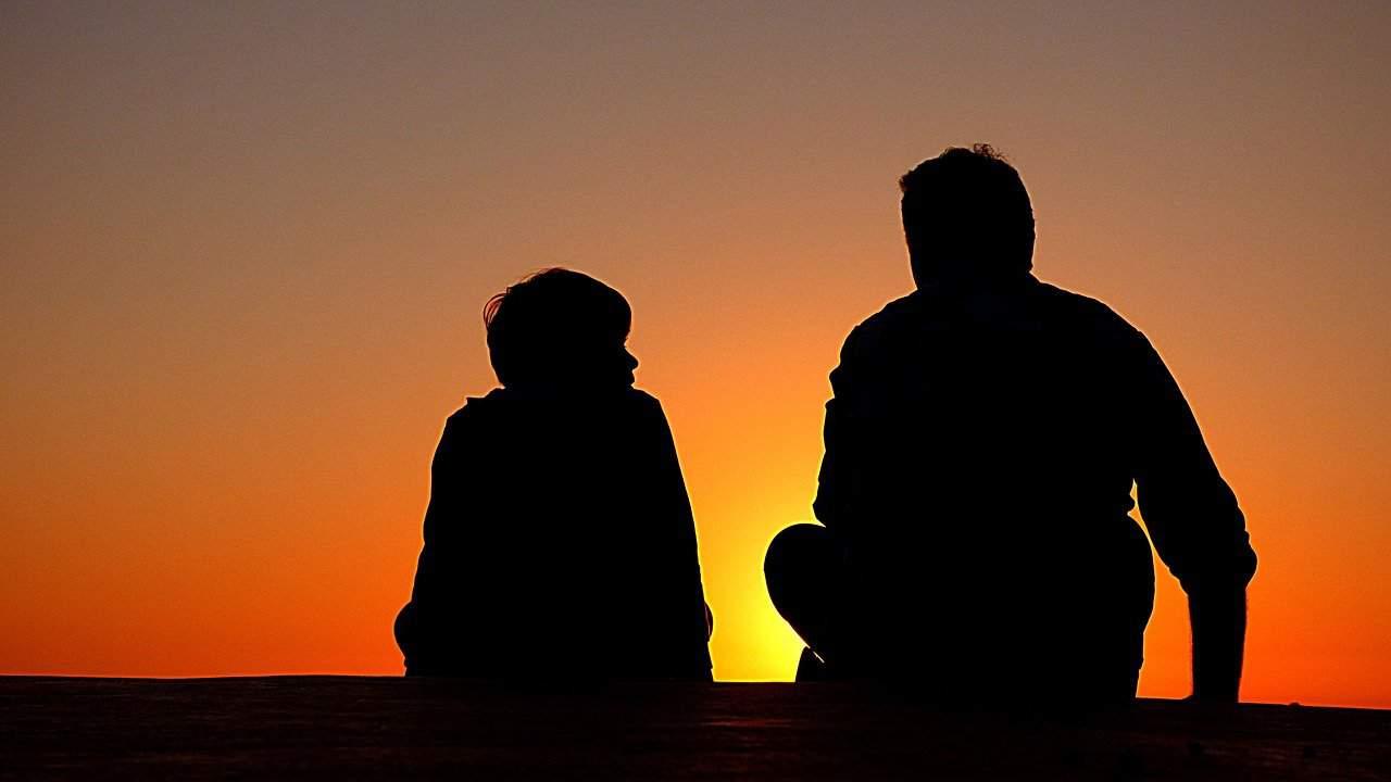 זוג צלליות של שני אנשים יושבים מול השקיעה