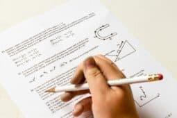 יד אוחזת עיפרון על גבי דף מבחן