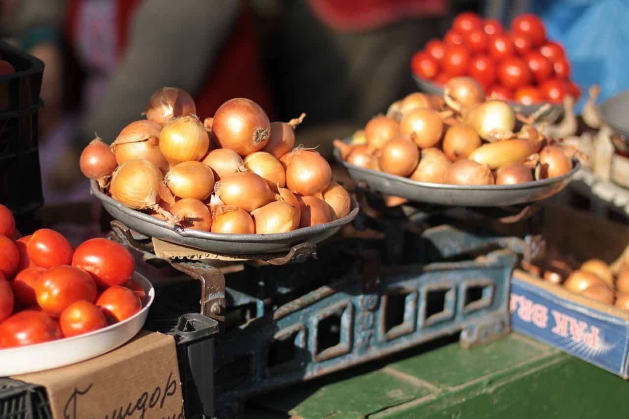 מאזניים בחנות ועליהם בצלים ועגבניות