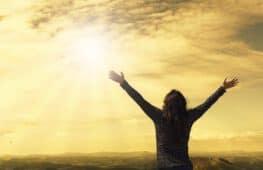 אישה פורסת ידיים מול השקיעה מתוך אושר