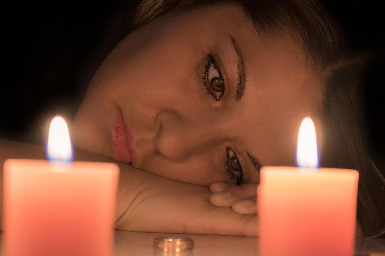 אישה מביטה בטבעת נישואין בפנים עצובות לאור נרות